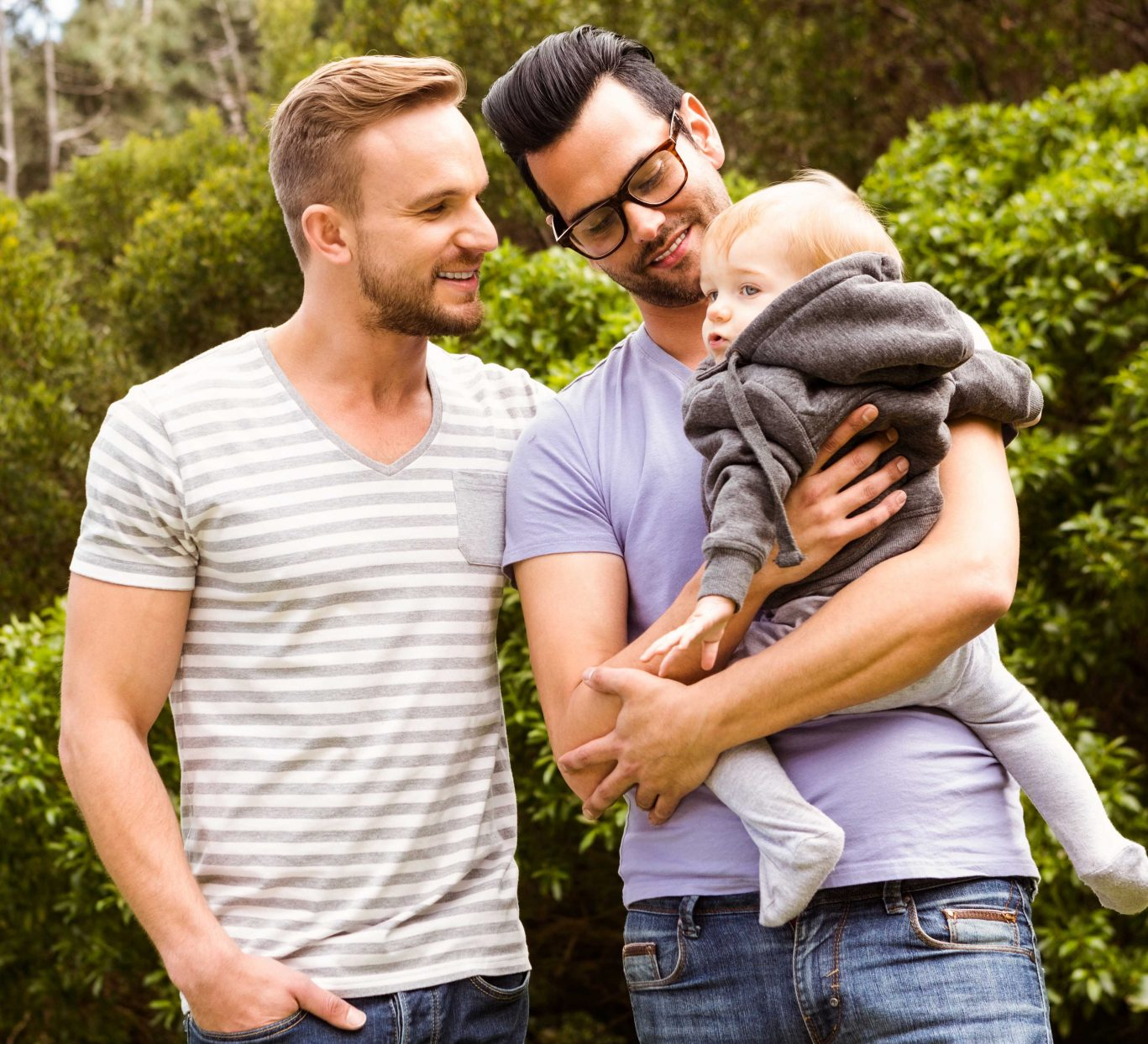 Smiling male couple holding baby